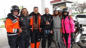 Riders on the road in rain gear during a gas stop on the ride.